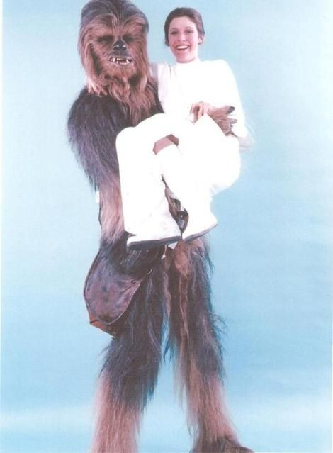 """Chewbacca actor Peter Mayhew recently shared his favorite candid photos from the set of the original """"Star Wars"""" films -- like this one of himself and Carrie Fisher who played Princess Leia"""" with personalized captions on his Twitter feed - TheWookieeRoars."""
