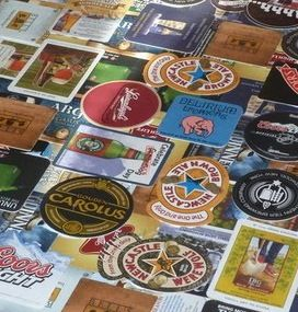 Example of how to layer beer brewery coasters to make a collage for a table top or wall hanging