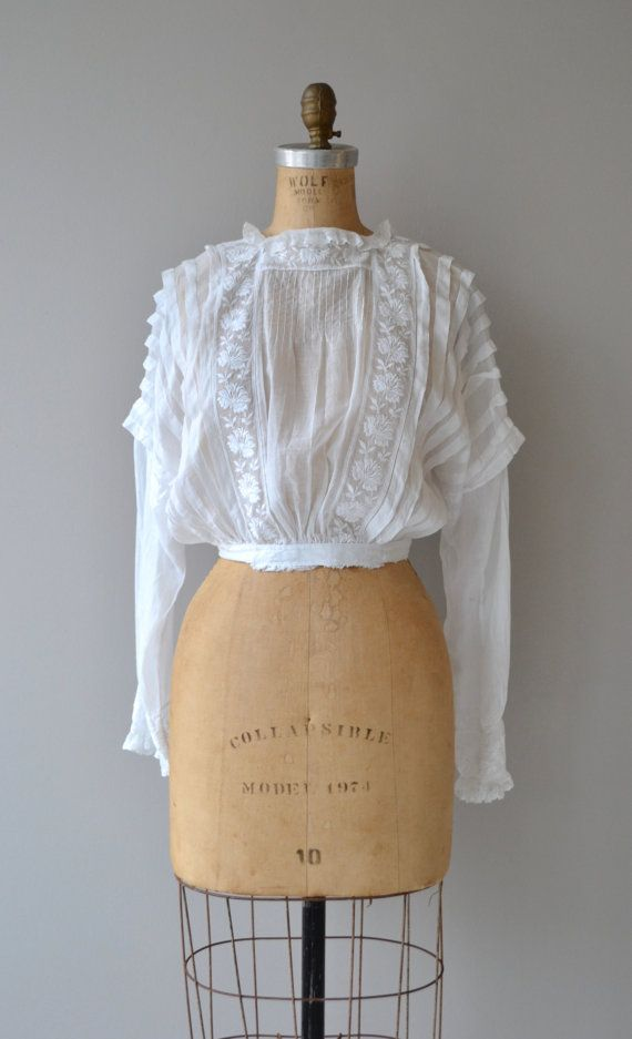 Antique 1910s Edwardian semi-sheer cotton blouse with interesting pleated shoulders and half sleeve, floral detail, banded waist and button back. --- M E A S U R E M E N T S ---  fits like: small bust: fits most waist: 26 length: 17 at the front / 15 at the back brand/maker: n/a condition: excellent  ✩ layaway is available for this item  To ensure a good fit, please read the sizing guide: http://www.etsy.com/shop/DearGolden/policy  ✩ more vintage dresse...