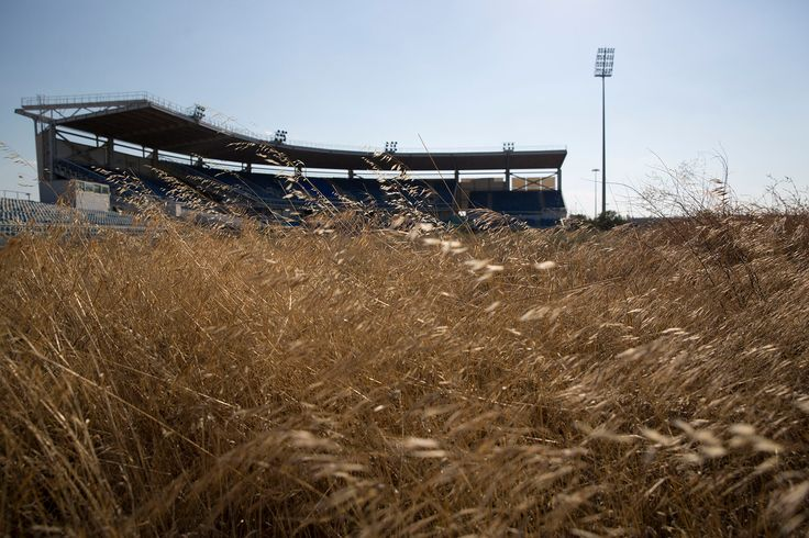 An abandoned stadium used for baseball events during the 2004 Olympic games is seen through weeds at the old airport in Athens on July 16, 2015.