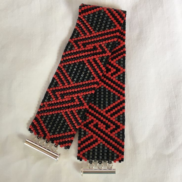 "A wonderful Peyote (Gourd) stitch bracelet in a geometric design using Black, Gray and Red colored Miyuki Delica beads. 1"" wide and 7"" long with a 3 ring Sterling Silver tube clasp. All the Peyote bra                                                                                                                                                     More"