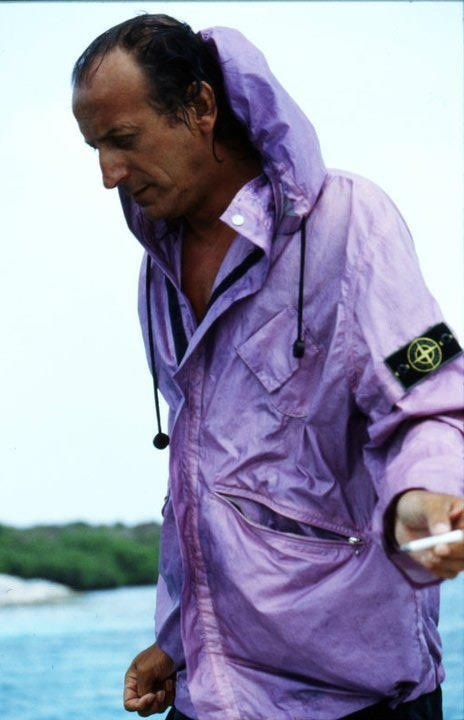 Massimo Osti testing purple ice jacket on beach on the coast of italy, near bologna, 1988. Smoking benson and hedges filter tipped medium tar in off white and tan.
