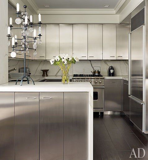 The kitchen of a Manhattan apartment features stainless-steel cabinets offset by Calacatta gold marble counters.