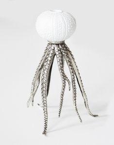 Vacker och unik ljusstake. Porslinsdel med ljushållare i form av sjöborre som står på bläckfiskarmar i metall. Finns i två utföranden: vit sjöborre med bläckfiskarmar i silver eller grå sjöborre med bläckfiskarmar i mässing.  Mått: djup ca 20 cm, höjd ca 25 cm