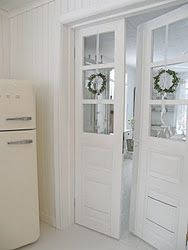 Pretty doors with wreaths, leading into the dining room from the kitchen