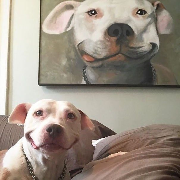 27 photos of animals proving that life imitates art - Smiling dog with portrait behind him.