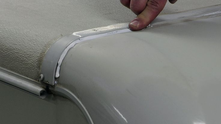 Learn how to use outdoor silicone to quickly seal the front cap on your roof in this RV roof repair demonstration.