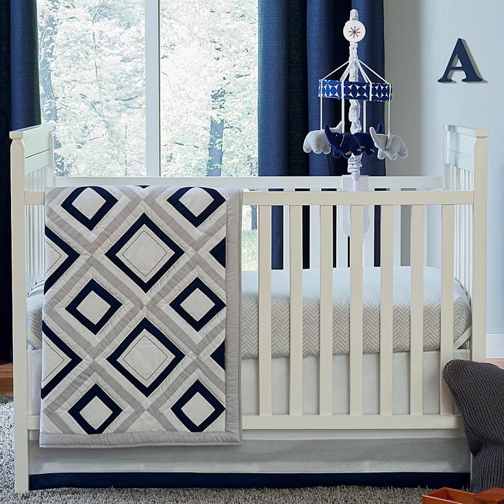 Happy Chic Baby by Jonathan Adler Taylor 4-Piece Crib Bedding Set. This modern 4-Piece Crib Bedding Set includes: a comforter, dust ruffle, crib sheet, and nursery organizer. Let's go geo with this stylish contemporary crib bedding set featuring a comforter with a geometric white, navy, and gray pattern, white crib sheet with gray chevron print, coordinating dust ruffle with bold stripes of solid white, gray, and navy and a patterned navy and white nursery storage to help keep baby's...