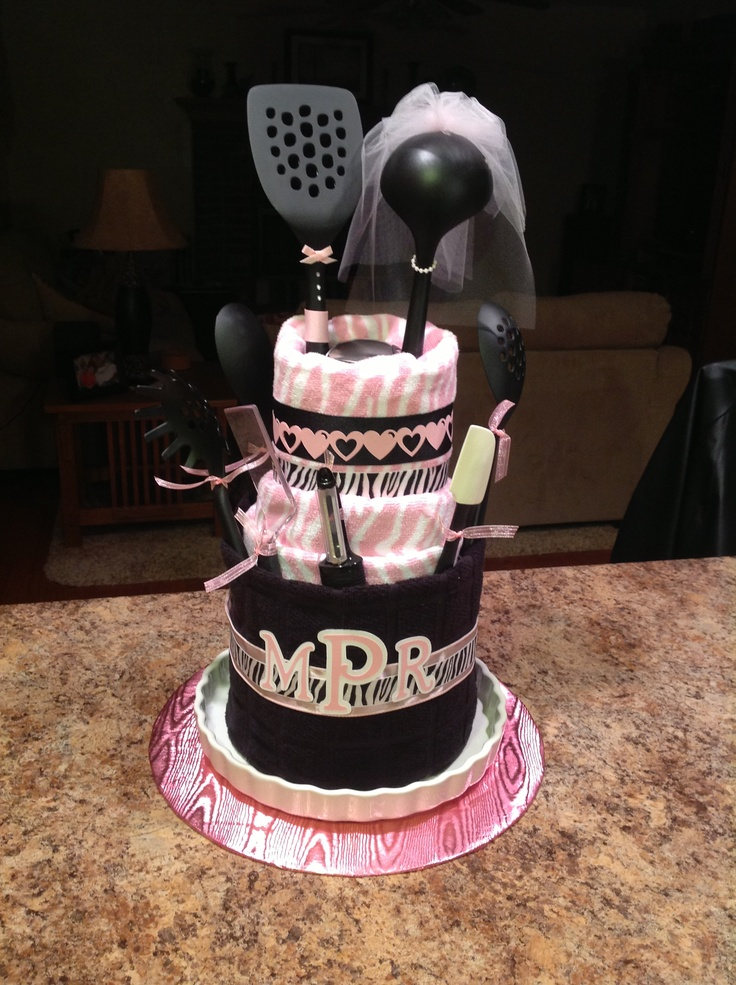 Megan's Bridal Shower Cake ...made from paper towel holder, 6 dish towels, 2 dish cloths, numerous utensils and kitchen gadgets and assorted ribbons. Embellish with monogram of happy couple. All items from the gift registry in the colors of the wedding!!