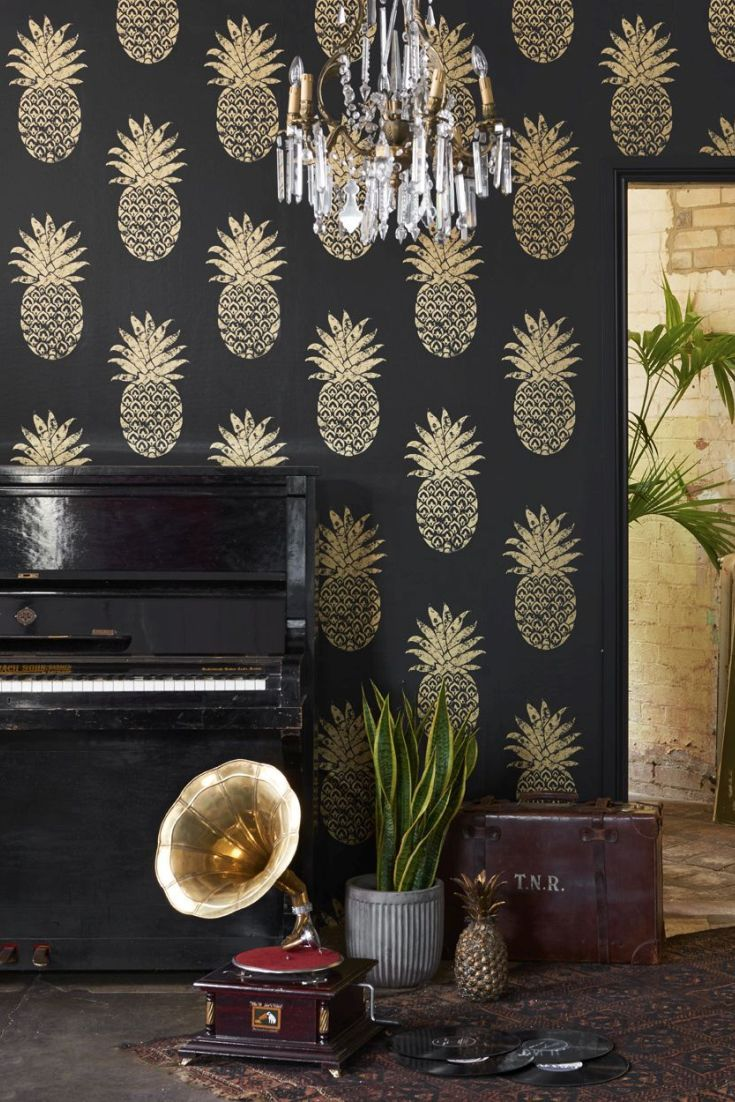 A large scale pineapple motif wallpaper with a hand-printed effect. Shown in metallic gold on ebony black.