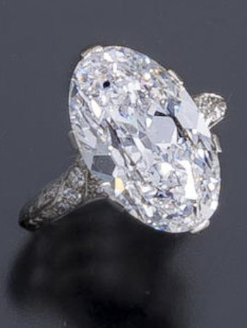 A belle époque diamond solitaire ring, circa 1915. The oval-shaped diamond, weighing 6.98 carats, within a delicate openwork mounting of single-cut diamonds; mounted in platinum.