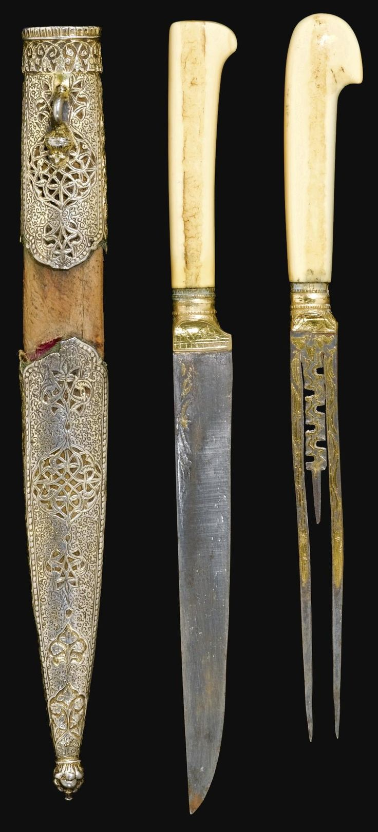 Ottoman knife and fork set (trousse), 19th century, both with marine ivory hilts, the steel knife and foliate pronged fork overlaid with gold and engraved at the forte, wood scabbard with faceted silver-gilt mounts engraved with an arabesque of spiraling scrolls and palmettes, openwork medallions bordered by floral scrolls, bud terminal and foliate suspension loop 27.5cm.