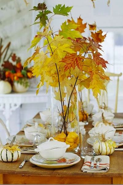 Simple fall twigs with leaves in a glass vessel with little pumpkins.  Could also use acorns, nuts, etc.