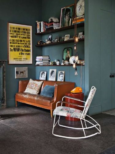 Dark teal walls, objects displayed on open shelves and a bright orange sofa by Retrouvius Reclamation and Design