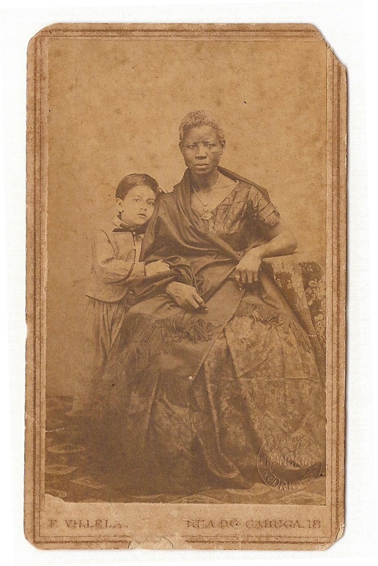 From one of the largest brazilian photo collections, a white boy with his black wet nurse. Her name was Monica and she's depicted here with her best clothes, which were made to show her position (being a wet nurse to a wealthy family was a prestigious occupation) as well to honour her employees/owners' house and name. Unknown date.