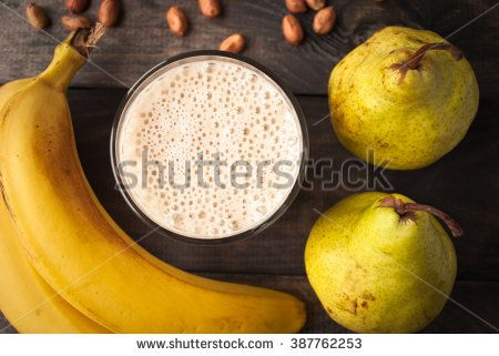 Glass of smoothie, some peanuts, fresh bananas and pears on wooden background. Close up
