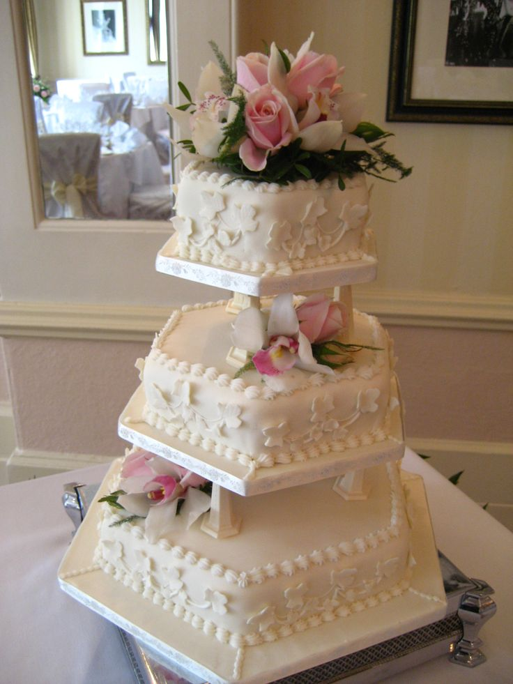 Pale Pink Orchid and Rose heads decorating a 3 tier hexagon Wedding Cake.