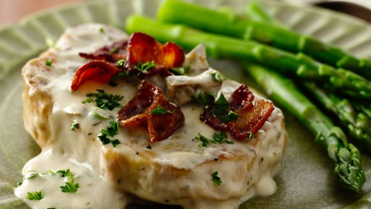 """Smothered pork chops have met their match! Bacon, sour cream and Progresso® Vegetable Classics creamy mushroom soup make a """"smothering-good"""" rich and creamy sauce."""
