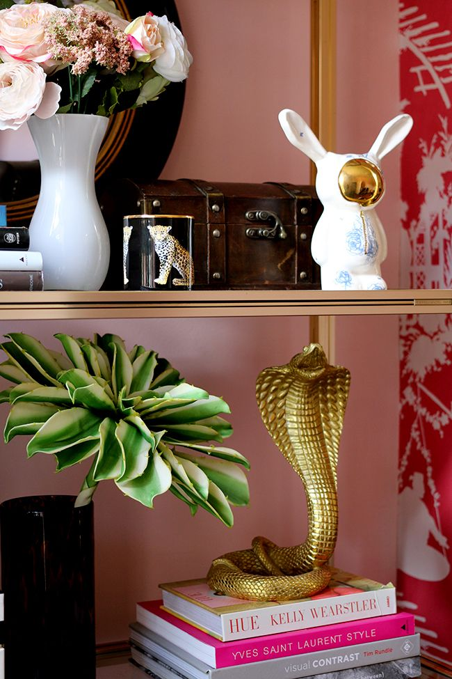 Halcyon Days Leopard Jasmine Scented Candle on brass shelf with pink walls