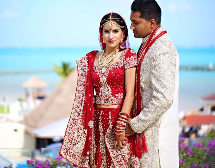 The lovely Nikyta is picture perfect in her pretty red bridal lehnga and matching kundan set with élan! The groom rocking his cream-colored sherwani and well-coordinated pagri looked equally as dashing. | #destinationwedding at Moon Palace Cancun