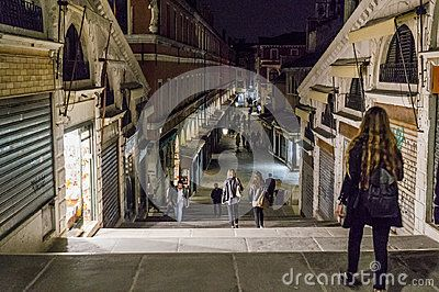 Rialto bridge with people and shops   in Venice , Italy. Europe . Night photography.