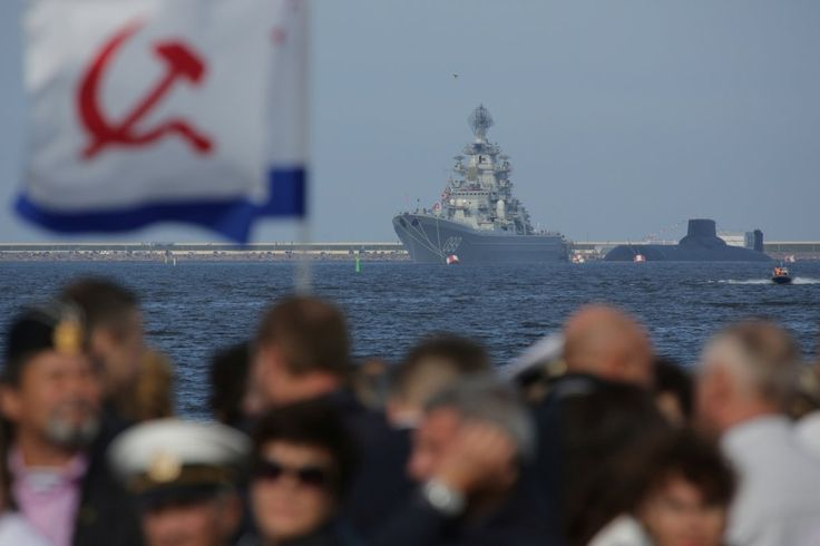 A Russian nuclear missile cruiser, Pyotr Veliky (Peter the Great), and nuclear submarine, Dmitry Donskoy in the background, sail towards St. Petersburg, as people gather to watch.