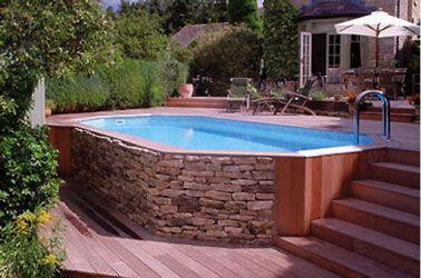 Une piscine hors sol en bois sertie de pierre sur la terrasse