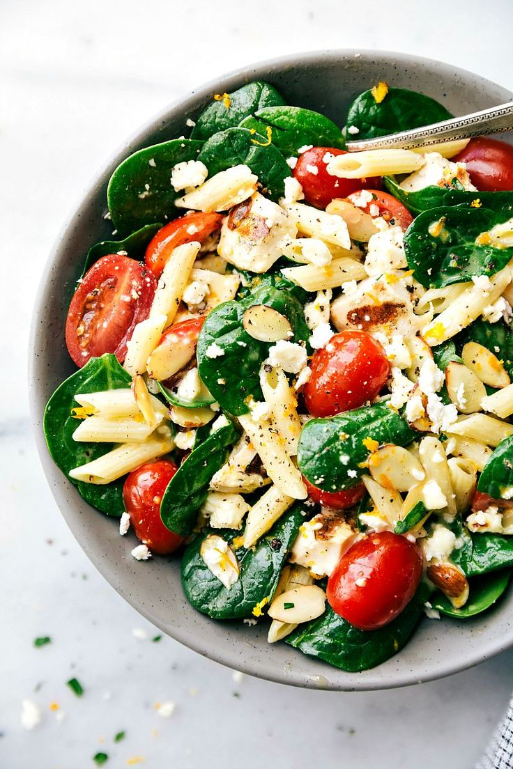 This is a spinach salad with penne pasta, grilled chicken, cherry tomatoes, toasted slivered almonds and a fresh citrusvinaigrette.