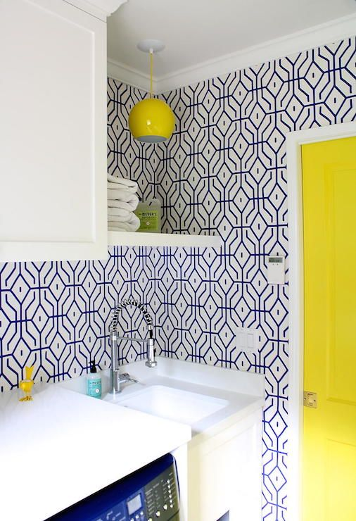 A yellow pocket door opens to a yellow and blue laundry room boasting walls clad in blue geometric wallpaper, Anna Spiro Rosey Posey Trellis Wallpaper in Ginger Jar Blue, lined with an enclosed blue washer and dryer tucked under cabinets beside a small utility sink paired with a pull-out faucet under shelf illuminated by a bright yellow light pendant.