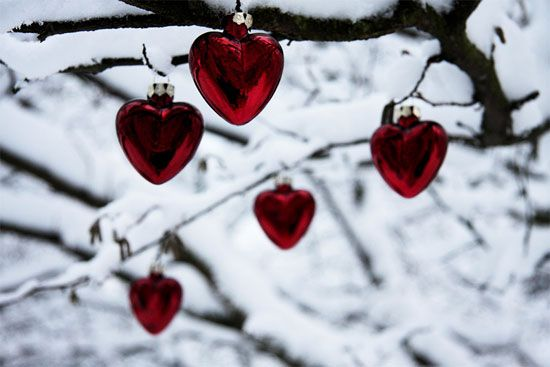 Heart-shaped Christmas ornaments on a snowy tree