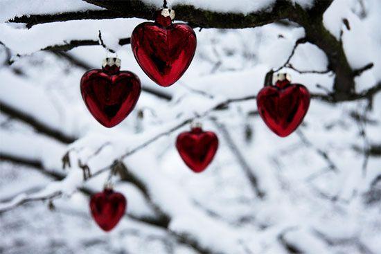 Heart-shaped Christmas ornaments on a snowy tree