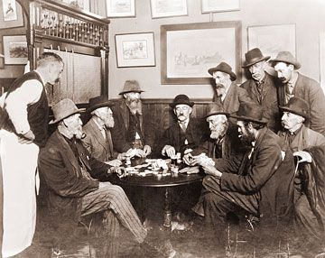 Men playing poker in a saloon in the old west, 1913