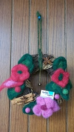 Ghirlanda con fiori di lana cardata, cannella e anice stellato