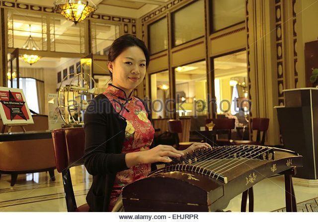 Woman playing a Guzheng a traditional Chinese music instrument in the lobby of Fairmont Peace Hotel, Shanghai China - Stock Image