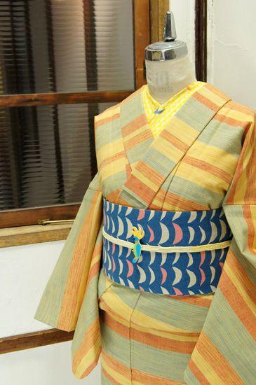 生成り色に色鉛筆で描いたようなカナリアイエロー、ポピーレッド、スカイブルーのボーダーが織り出されたウールの単着物です。