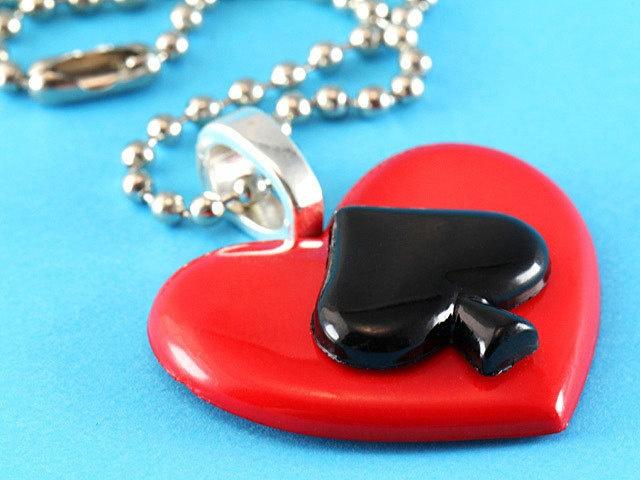 Rockabilly stijl ketting met een groot rood hart en een zwarte schoppen aas.    - Hart is ongeveer 3.2 x 2.9 cm  - Lengte van ketting is 46 cm  - R...