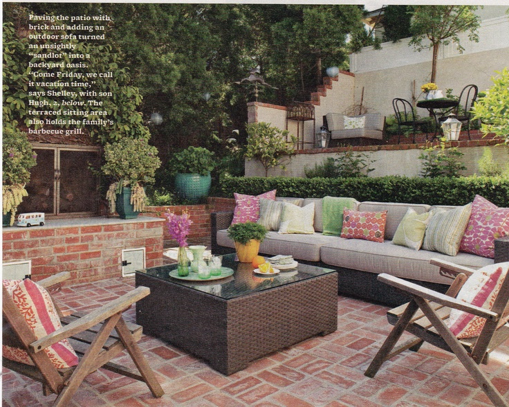 Paving the patio with brick and adding an outdoor sofa turns an unsightly sandlot into a backyard oasis.