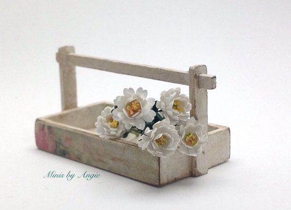 White chrysanthemums with leaves. Shabby wooden basket with flowers. Miniature