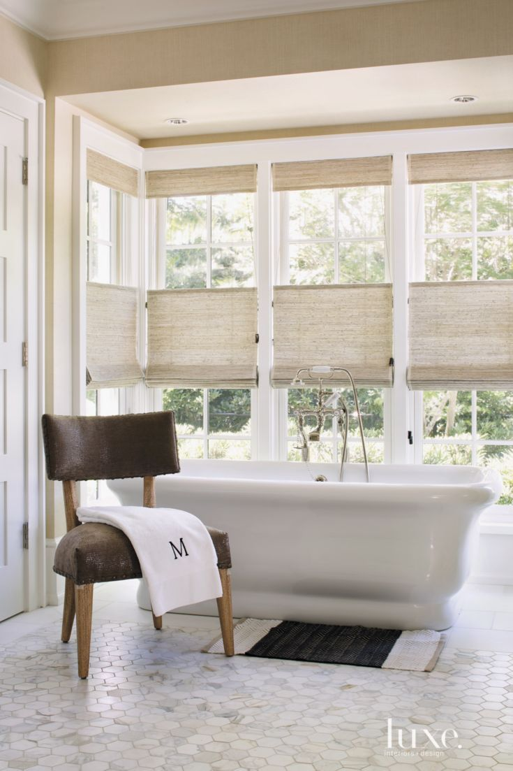 Partial shades by Hartmann&Forbes provide privacy for soaking in the master bathroom's original freestanding tub. The chair is by Lee Industries.