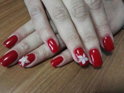 Nail art rosso con fiore in acrilico bianco e microperline argento
