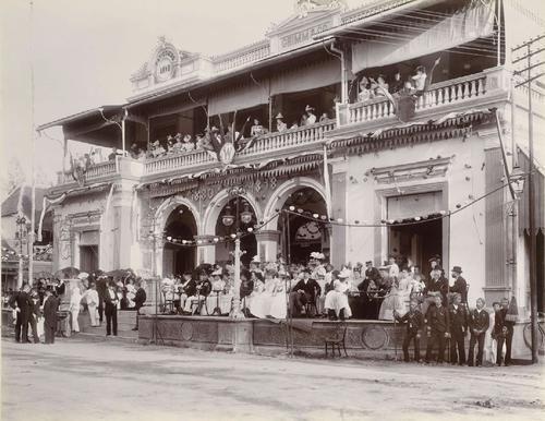 Toeschouwers wachten op het bordes van de patisserie Grimm & Co aan de Pasar Besar in Soerabaja op de optocht ter gelegenheid van de inhuldiging van Wilhelmina | Colonial