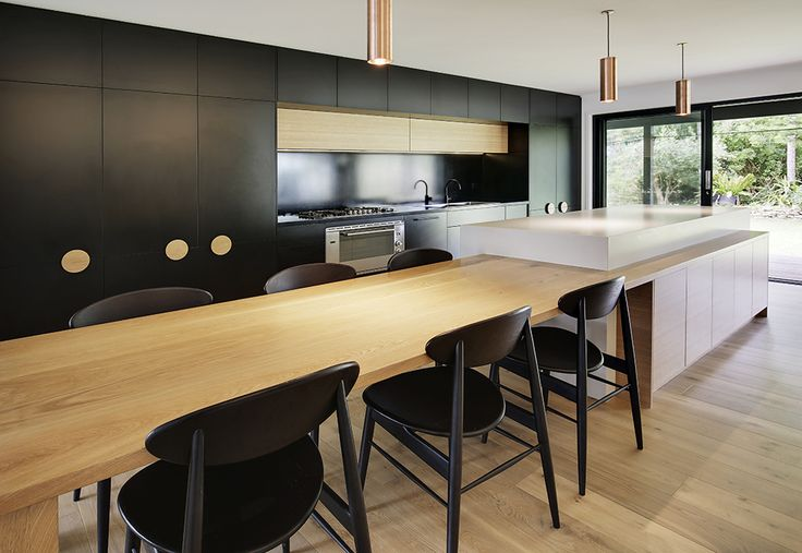 European Style Kitchen with polytec Black Matt Melamine doors alongside American Oak solid timber table with fresh concrete Caesarstone island and black Corian cook top bench