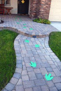 Dinosaur Footprints! Last year I made a stencil of a footprint and colored it in with green chalk. The kids loved following the footprints to the door and it set the stage for the rest of the dinosaur themed party! Note: this is not my picture it looks like they used paper foot prints.