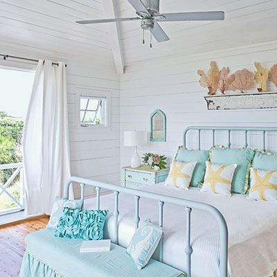 """Understated Bedroom: A piece of salvaged crown molding serves as a shelf and holds a collection of sea coral. The homeowner scoured flea markets and integrated her finds into the decor. """"I sought things that would lend a sense of history: old windows, mirrors, side tables, cabinet doors, and dressers,"""" she says. She then used paint to freshen furnishings and give them a coastal vibe."""
