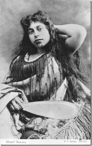 Shows young Maori woman with fringed cloak, grass skirt, patu, and moko.