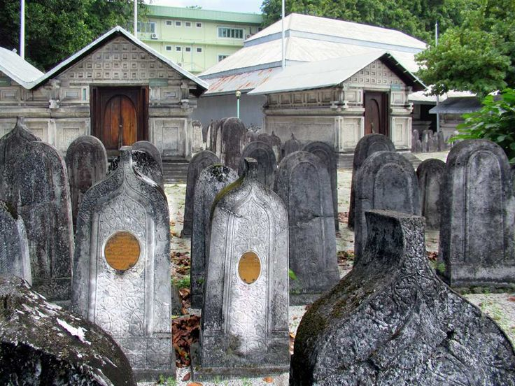 Tombstones fill the courtyard of the Old Friday Mosque or Hukuru Miskiiy (1656) in Male, Maldives. Those with pointed tops are for males, those with rounded tops for females. The small buildings are family mausoleums.