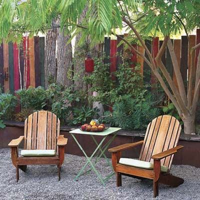 two Adirondack chairs and a small table nestled under the trees in front of a wood fence and plantings