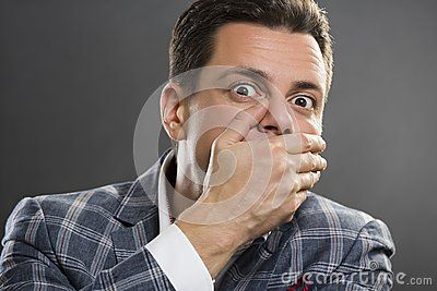 Portrait of afraid businessman wearing suit covering his mouth with his hand over grey background.