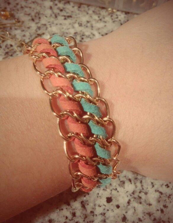 Pulsera con cadena dorada y cueros coral y turquesa.