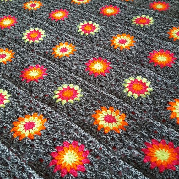 This lovely retro vintage style blanket is constructed using 120 squares with floral or sunburst centers using 3 different colors all set in gorgeous background of grey. There are 10 rows of 12 squares. The blanket measures approx 52 x 62. The border incorporates all the neon colors pink,yellow & orange. Made using good quality acrylic yarn it is both soft, snuggly and warm. Machine washable and can be dried at low heat, though also air dries very quickly as well. Handmade in Scotland…